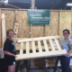 Amy Smith, left, and daughter Allie of Healthy Homeworks move a bed frame part at the nonprofit's facility in the Pepperell Mill in Lewiston.
